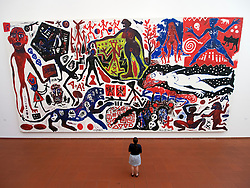 Woman looking at painting painting Ich in Deutschland by A R Penck  on display at Museum Ludwig in Cologne Germany