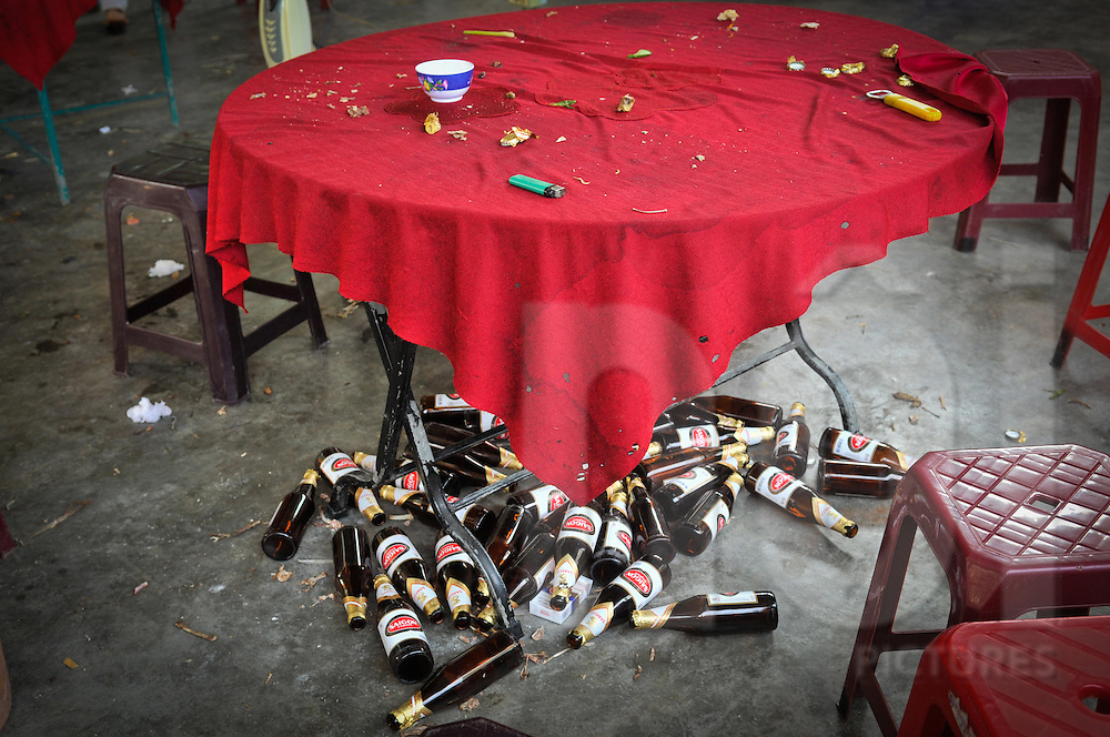 Vietnamese restaurant at the end of the meal. The red tableclothe is very dirty and a lot of beer bottles strew the ground