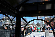 Viewed from a bus shelter, people line up outside of the Rochester Opera House in Rochester, NH to attend Democratic presidential candidate, Hillary Rodham Clinton's town hall meeting Friday, Jan. 22, 2016.  CREDIT: Cheryl Senter for The New York Times