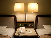 nightstand with phone paper and pencil between two beds in a hotel room