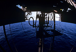 Stock photo of a silhouette of a man working under a jack up rig