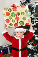 Boy (5-6) in Santa costume holding present over head