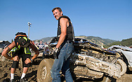NEWS&GUIDE PHOTO / PRICE CHAMBERS.Shaun King glances at the cheering crowd as he inspects the smashed front end of his derby car. Last year's winner couldn't pull it off this time although two of the team's other cars placed second and third after a car suspected of cheating.