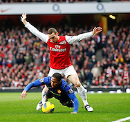 Picture by Andrew Tobin/Focus Images Ltd. 07710 761829. .21/01/12. Thomas Vermaelen (5) of Arsenal clashes with Luis Antonio Valencia (25) of Manchester United during the Barclays Premier League match between Arsenal and Manchester United at Emirates Stadium, London.