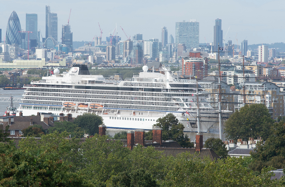 ©Licensed to London News Pictures 30/08/2019.<br /> Greenwich ,UK. The Cutty Sark in the foreground as the Viking Sun cruise ship from Norway is pulled backwards down the River Thames this afternoon so it can dock next to the Cutty Sark in Greenwich, London.  Photo credit: Grant Falvey/LNP