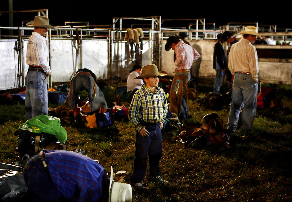 A Young bullrider waits in the paddock with older bullriders as they prepare for their ride at the Casino Showground during Beef Week celebrations. Casino is a Cattle town in northern NSW, Australia.