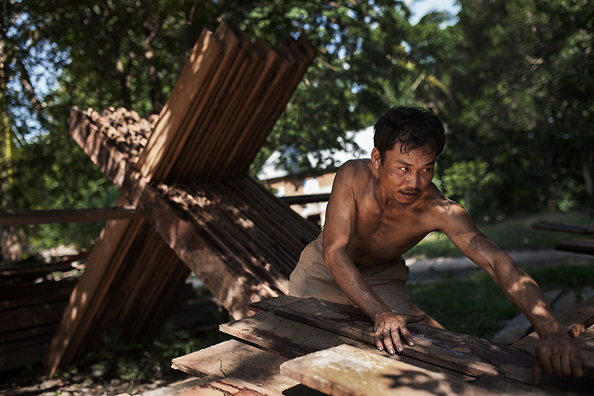 A villager from Srae Sronok storing wooden planks which he will use in the months to come to re-build a house in the new relocation site. The villagers were offered two options: either accept $6000 per family and re-build a house by themselves or move into a small concrete house with a tin roof and 5 hectares of land to farm. Like many other promises though, no official document has been yet provided. Stung Treng, northern Cambodia.