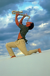 man on a sand dune playing a saxophone