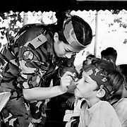 A female Government soldier puts camouflaged cream on a boys face during a programe aimed at 'winning hearts and minds'. The concept of the programe was to teach the youngsters that the army offered a better future than the rebel groups. The 'open days' at the army base allowed the children to be soldiers for a day and gave the military achance to gather information about the local people.<br />
