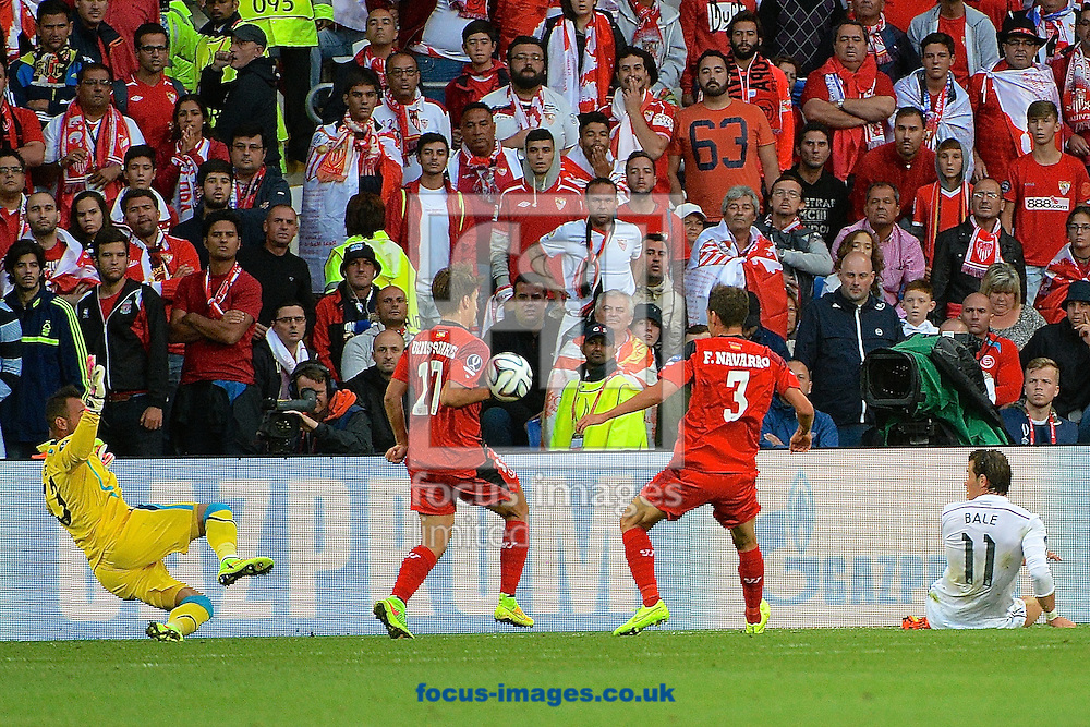 Denis Su&aacute;rez of Sevilla blocks a hot from Gareth Bale of Real Madrid with his hand during the European Super Cup match at the Cardiff City Stadium, Cardiff<br /> Picture by Ian Wadkins/Focus Images Ltd +44 7877 568959<br /> 12/08/2014
