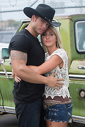 sexy cowboy holding a blonde girl by an old pick up truck
