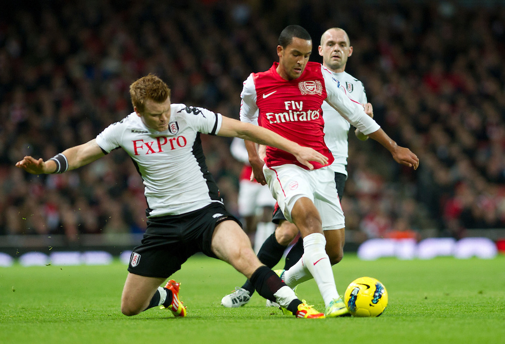 Arsenal's Theo Walcott figts for the ball with Fulham's John Arne Riise during  their English Premier League during  their English Premier League soccer match at the  Emirates stadium in London, Saturday, Nov. 26, 2011. (AP Photo/Bogdan Maran)