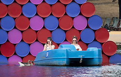 © Licensed to London News Pictures. 27/07/2018. London, UK. People ride pedal boats on the Serpentine in front of artist Chirsto's installation 'The London Mastaba' in Hyde Park ahead of an expected break in the heatwave.  Rain is expected in parts of the south later. Photo credit: Peter Macdiarmid/LNP