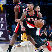 26 March 2016: Portland Trail Blazers guard Damian Lillard (0) drives past Los Angeles Lakers guard D'Angelo Russell (1) on a screen set by Portland Trail Blazers forward Noah Vonleh (21) during the Portland Trail Blazers 97-81 victory over the Los Angeles Lakers, at the Staples Center, Los Angeles, California, USA.