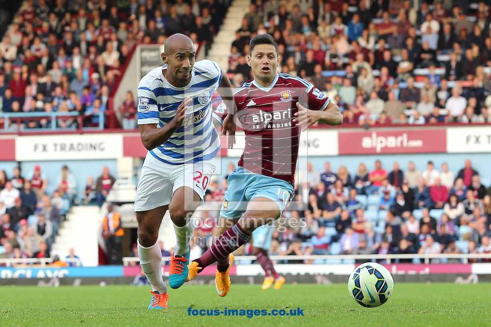 Mauro Zarate of West Ham United and Karl Henry of Queens Park Rangers during the Barclays Premier League match at the Boleyn Ground, London<br /> Picture by Richard Calver/Focus Images Ltd +447792 981244<br /> 05/10/2014