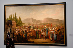 "© Licensed to London News Pictures. 21/04/2017. London, UK.  A staff member views ""The Arrival of the Mahmal at an Oasis en Route to Mecca"", circa 1805-25, by Georg Emmanuel Opiz, (est. GBP 0.8-1.2m), at a preview at Sotheby's, New Bond Street, of upcoming sales of Arts of the Islamic World, 20th century Middle East Art and Orientalist art. Photo credit : Stephen Chung/LNP"