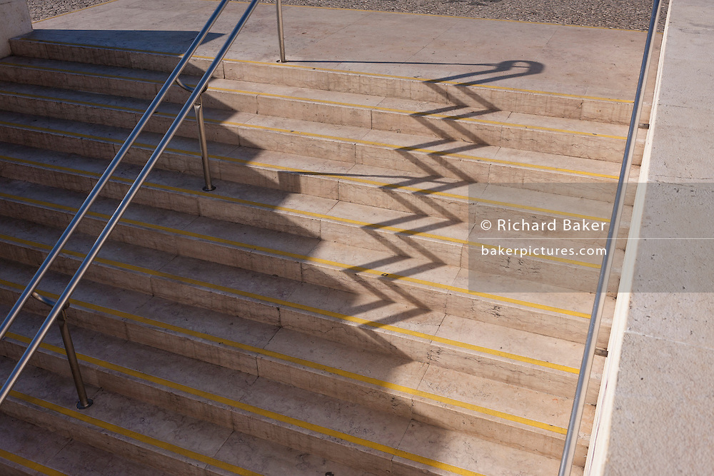 An abstract landscape of zigzag shadows of steps at Alameda metro station, Lisbon, Portugal.