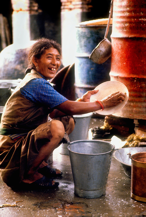 A woman in Tibetan style clothes washes dishes in a bucket near the Swyambhu temple complex in Nepal's Kathmandu Valley.