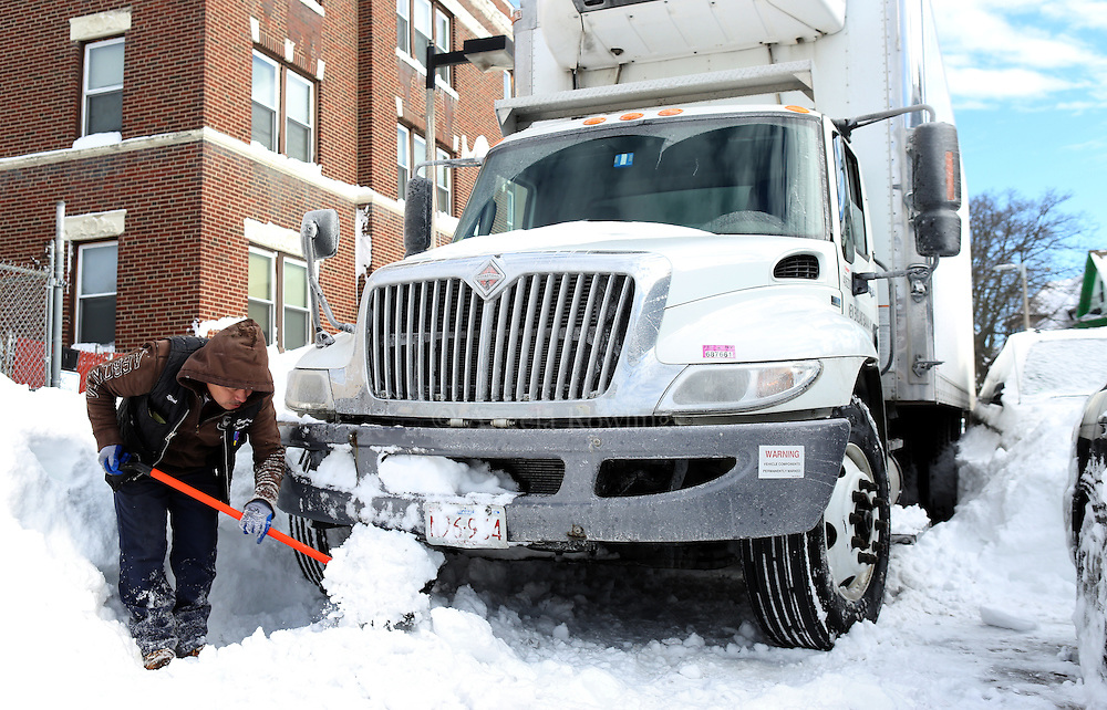 (Boston, MA - 1/28/15) A truck driver clears snow from under his wheels after he got stuck on a side street in Dorchester, Wednesday, January 28, 2015. Staff photo by Angela Rowlings.