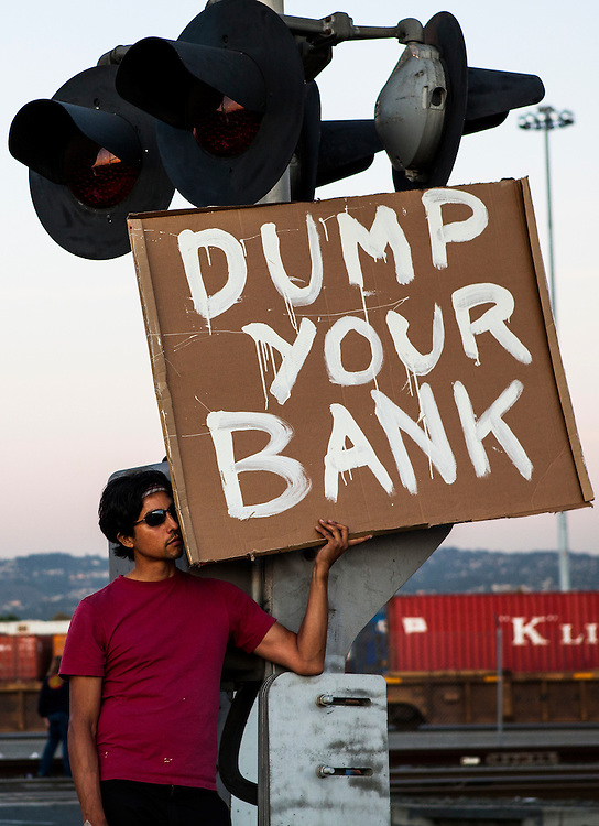 OAKLAND, CA - NOVEMBER 2, 2011: A man holds a sign as he rests from marching to the Port of Oakland from downtown Oakland. The Occupy movement shutdown the Port of Oakland.