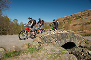 Cycllists riding over Ashness Bridge in Borrowdale,  Lake District National Park, Cumbria, UK