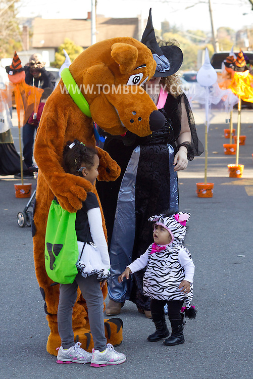 Middletown, New York  - Children stand next to a costumed character at the Halloween Fall Festival at the Middletown YMCA's Center for Youth Programs on Oct. 25, 2014.