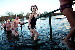 Serpentine Christmas Day Swimming. Members of the Serpentine Swimming club exit the water after taking part in the annual Peter Pan Cup - Christmas Day race in the  Serpentine lake.  The swimmers compete in a 100 yard swimming race which has taken place on Christmas Day every year since 1864.The Serpentine Lake, London, United Kingdom. Wednesday, 25th December 2013. Picture by Peter Kollanyi / i-Images