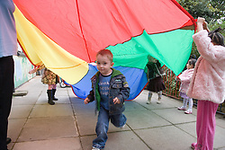 Little boy at playschool enjoying the parachute game,