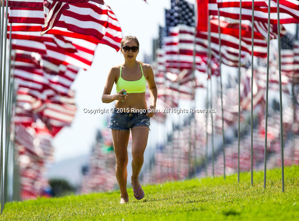 A woman runs through amongst 3,000 US flags are displayed at Pepperdine University to mark the 14th anniversary of the 9/11 terror attack, September 10, 2015 in Malibu, California.  Photo by Ringo Chiu/PHOTOFORMULA.com)