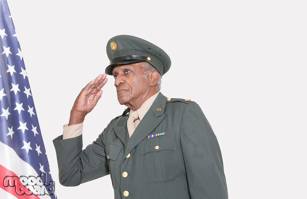 Senior male US military officer saluting American flag over gray background