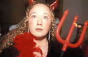 A girl in fancy dress, wearing devil horns and a pitch fork, UK 2004
