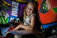 McKenzie (6) reads books at the children's makeshift den at home in Shefield UK Tuesday, Aug. 12, 2014The D'Arby family is involved in the FAST  (Families and Schools Together) program which encourages parents to read to their children at home.(Elizabeth Dalziel for Save the Children )