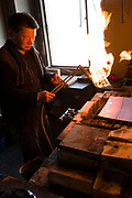 Annealing process while preparing the metal that will form the base for a cloisonne work. Ando Cloisonne, Nagoya, Aichi Prefecture, Japan, February 26, 2018. Family-owned and run Ando Cloisonne was founded in the 1880s and is the only large manufacturer of cloisonne metalware left in Japan. The cloisonne enamelling process is technologically complex and a single work may feature over 50 colours.