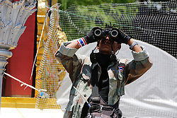 © Licensed to London News Pictures. 15/05/2014. A PDRC guard on patrol looks through his binoculars on the look out for snipers at a protest site near the site of a grenade and gun shots attack at Democracy monument in Bangkok on May 15, 2014. Grenade blasts and gunfire rocked an anti-government protest site in Thailand's capital, leaving two dead and 24 wounded as fears of wider political violence mounted in Bangkok Thailand. Photo credit : Asanka Brendon Ratnayake/LNP