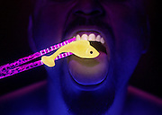 Man uses glowing chopsticks to hold a small glowing fish.Black light