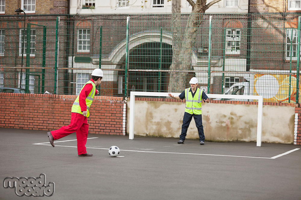 Two manual workers playing football