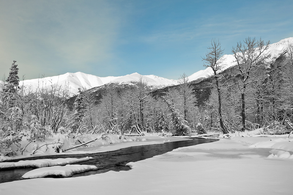 Landscape of Eagle River in Chugach State Park as it nears freeze-up in November with Chugach Mountains in background in Southcentral Alaska. Winter. Afternoon.