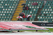 Umbrellas are up as a heavy rain shower passes over to further delay the start of play during the Specsavers County Champ Div 1 match between Somerset County Cricket Club and Essex County Cricket Club at the Cooper Associates County Ground, Taunton, United Kingdom on 25 September 2019.