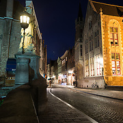 A street in the historic center of Bruges at night from a bridge over the canal.