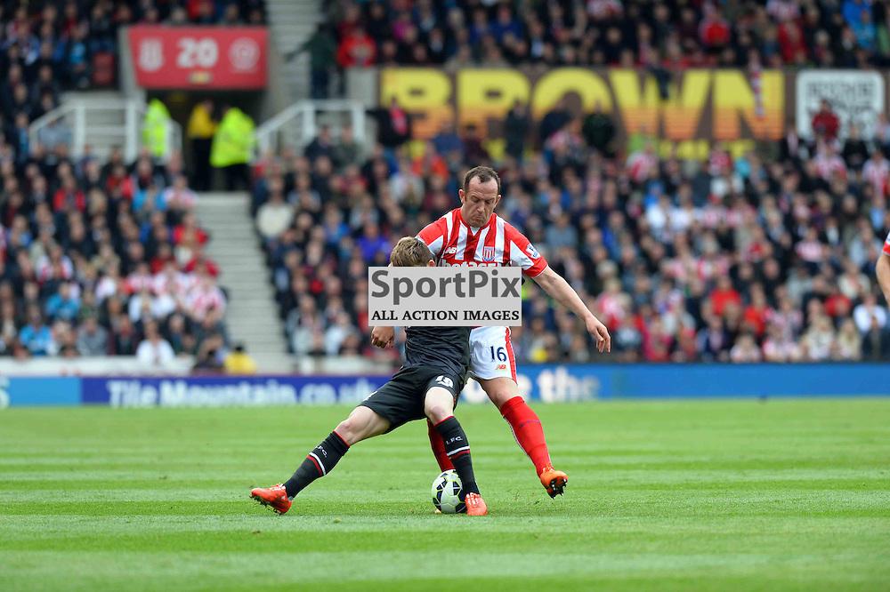 Charlie Adam of Stoke tackles Liverpool player Alberto Moreno
