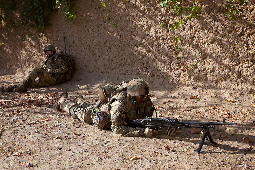 Soldier from 3 SCOTS (The Black Watch) wait just outside the doorway of a compound just seconds before  Private Stephen Bainbridge, aged 25, from Kirkcaldy becomes gravely wounded in an IED explosion in the same dorway which traumatically amputated his right leg and damaged his right so badly that it too later had to be amputated. His life was saved by the swift actions of Cpl John Goodie (21) a medic with 1 PWRR (The Princess of Wales's Royal Regiment) who applied tourniquets and first field dressings to get the bleeding under control. Private Chis Watson (21) also assisted in the treatment whilst reassuring the casualty and keeping him alert and responsive.  Once he had been stabilized the men CASEVAC'd Private Bainbridge to the MERT helicopter and he was rushed to Bastion Field Hospital.  Loya Manda, Nad e Ali, Helmand Province, Afghanistan on the 11th of November 2011.