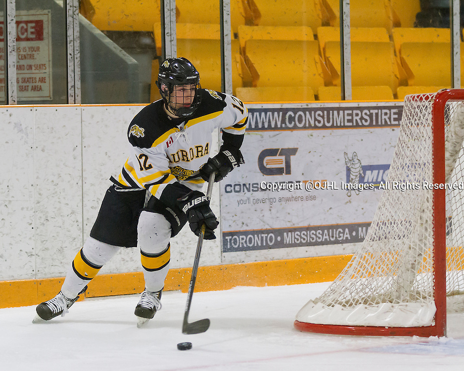 AURORA, ON - Feb 27, 2015 : Ontario Junior Hockey League game action between the Aurora Tigers and the Newmarket Hurricanes.  Game one of the best of seven series. Noah Delmas #12 of the Aurora Tigers carries the puck during the first period.<br /> (Photo by Stephen DiNallo / OJHL Images)