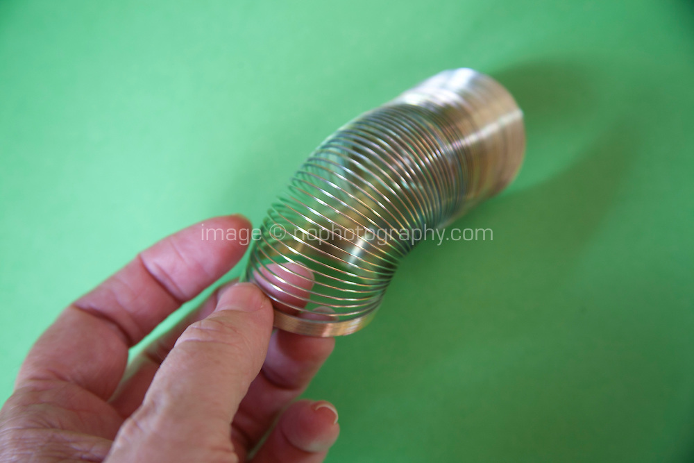 Hand moving Slinky or Lazy Spring toy made of a helical spring that stretches and can bounce up and down
