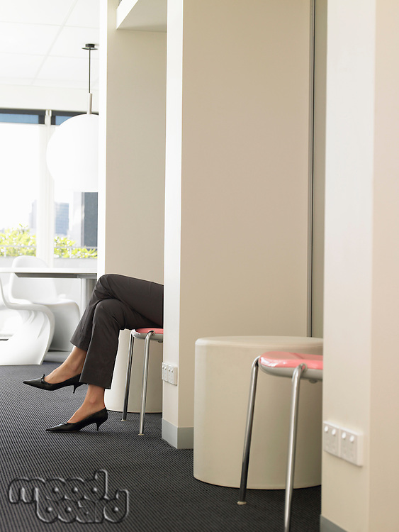 Businesswoman's legs sticking out of cubicle