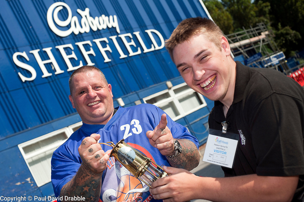 Cadbury 2012 Paralympic demonstration Sheffield..Steve Gill former soldier and Big Brother Contestant in 2010 and now coach and player with the Leicester Cobras Wheelchair Basketball team pictured with Torch Bearer Josh Dunn and the paralympic torch outside Kraft Foods (formerly Basset's factory) Sheffield...3 September 2012.Image © Paul David Drabble