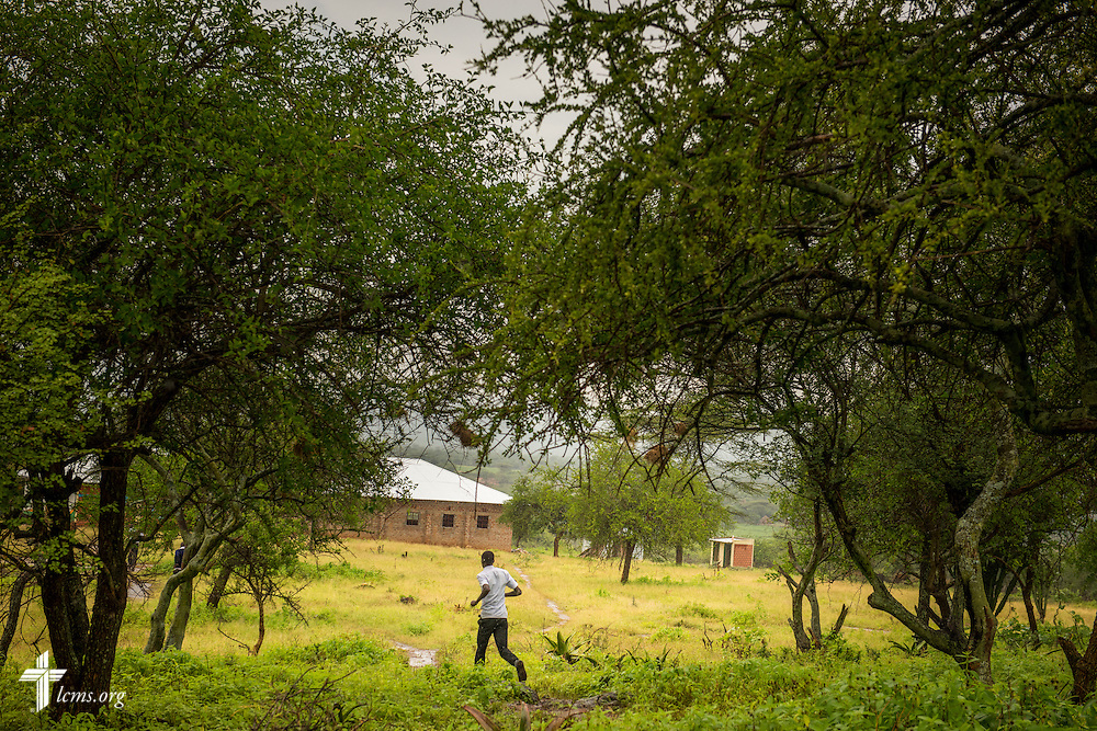 An older student runs to avoid the rain at the St. Augustine School on Friday, June 24, 2016, near Chepareria, Kenya. The school is home to a graduate of the U-Dom ELCK (Evangelical Lutheran Church in Kenya) Project 24 site. LCMS Communications/Erik M. Lunsford