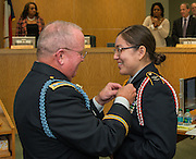 Lt. Col. Dennis O'Driscoll, left, presents Bellaire High School JROTC cadet Bianca Rubio Casteneda the Legion of Valor Bronze Cross during the Board of Education meeting, October 9, 2014.