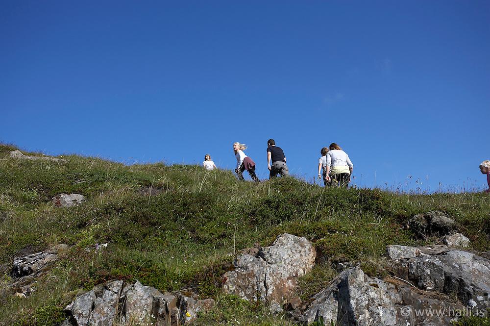 People hiking at the mountain Helgafell in Stykkisholmur, Iceland - Fólk að ganga á Helgafell í Stykkishólmi