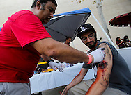 Makeup artist applies fake blood to a mock victim during the annual Great California ShakeOut earthquake drill at Southern California University (USC) in Los Angeles on October 15, 2015. About 10.4 million Californian's registered to take part in the annual drill that asks participants to 'drop'' to the ground, take 'cover'' under a desk, table or other sturdy surface, and 'hold on'' for 60 seconds, as if a major earthquake were occurring.(Photo by Ringo Chiu/PHOTOFORMULA.com)