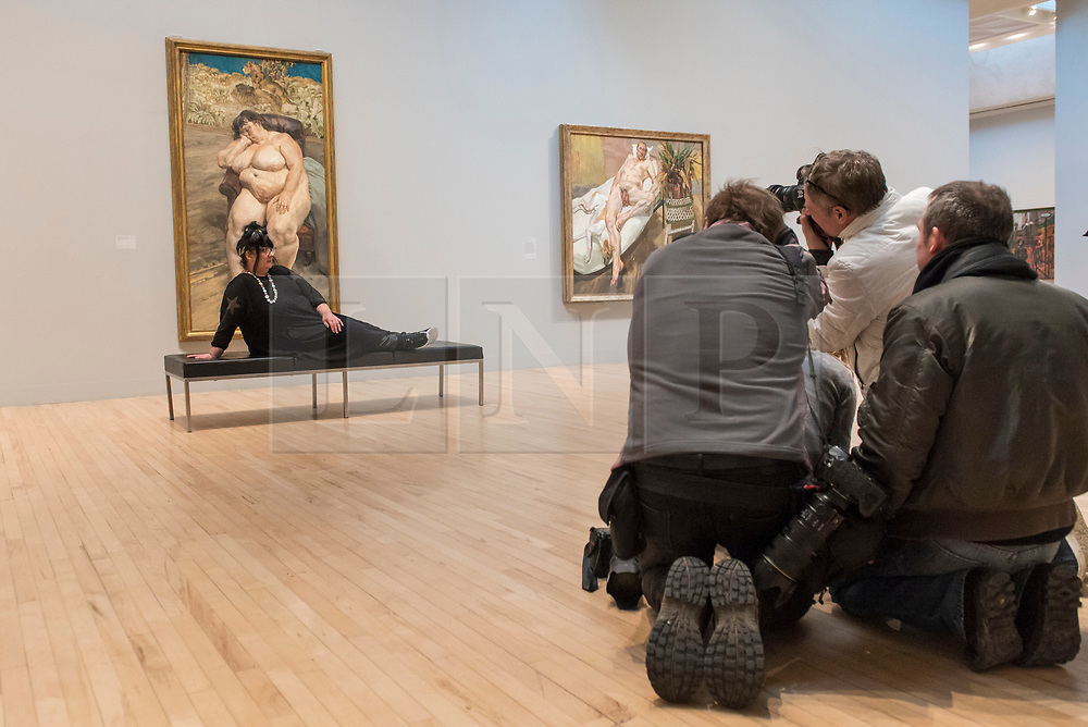 """© Licensed to London News Pictures. 26/02/2018. LONDON, UK. Sue Tilley is photographed sitting with a painting of herself by Lucian Freud """"Sleeping by the Lion Carpet"""", 1996. """"Preview of """"All Too Human"""", an exhibition at Tate Britain which explores how artists in Britain have stretched the possibilities of paint in order to capture life around them.  The exhibition runs 28 February to 27 August 2018 and includes rarely seen works by Lucian Freud and Francis Bacon.  Photo credit: Stephen Chung/LNP"""
